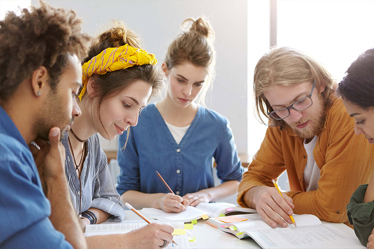 Four teenagers collaborating on paper work around a table